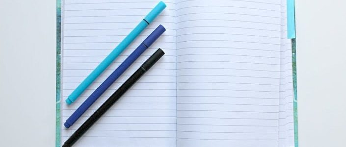 Photo of 3 pens on a notebook