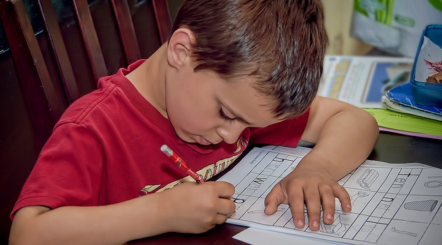 Boy in red T shirt studying in the classroom