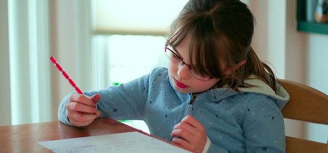 Girl with a blue jumper sitting at a table doing her homework