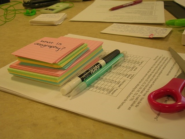 Post-it notes on a desk with pens and paper