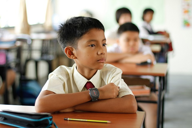 Boy wearing school uniform preparing for a test in school