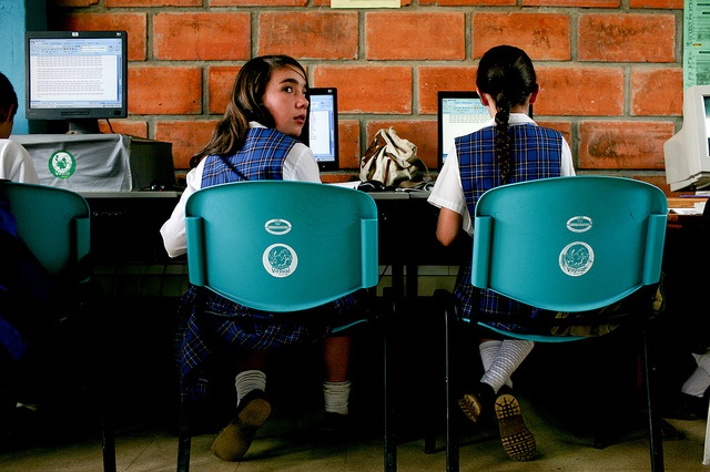Two girls in school uniform using computers