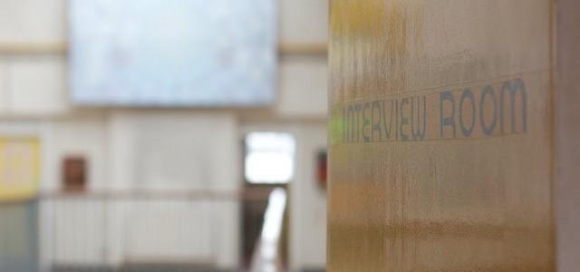 Interview room door with classroom table in background