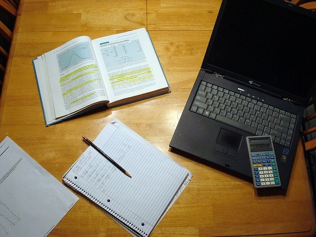 Desk with laptop, calculator, notepad and books