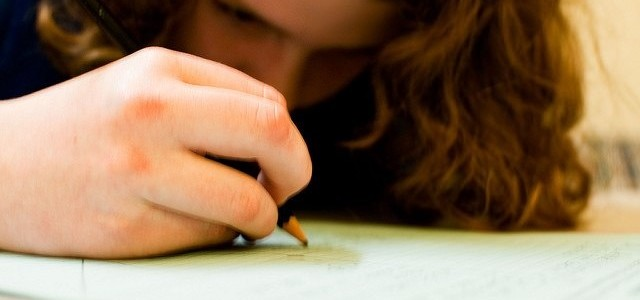 Girl writing on paper with a pencil