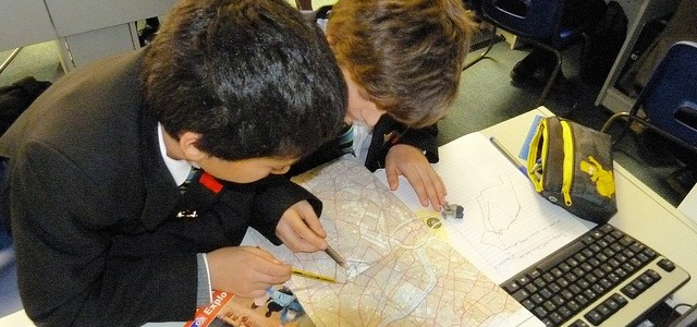 Two school boys studying a map
