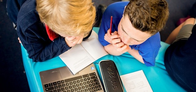 Two school children using a laptop