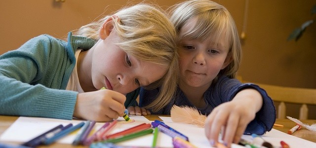 Two school girls colouring with crayons