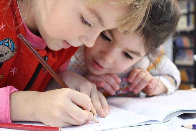 Photo of two girls writing in a book