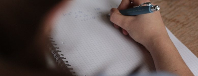 Photo of girl writing on notepad with pen