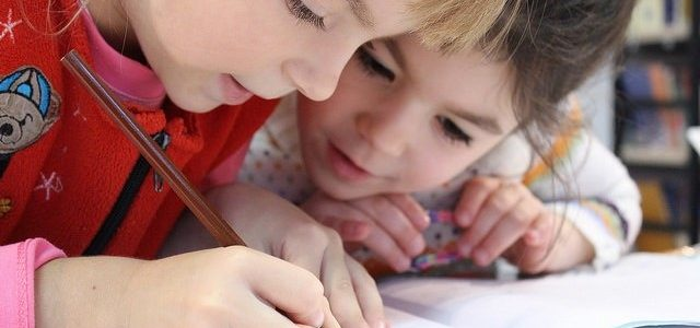 Photo of two girls writing in a school book
