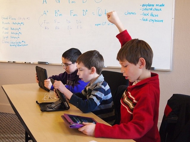 Photo of three boys sitting in a classroom