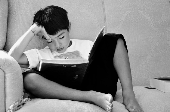 Photo of a boy reading on a chair