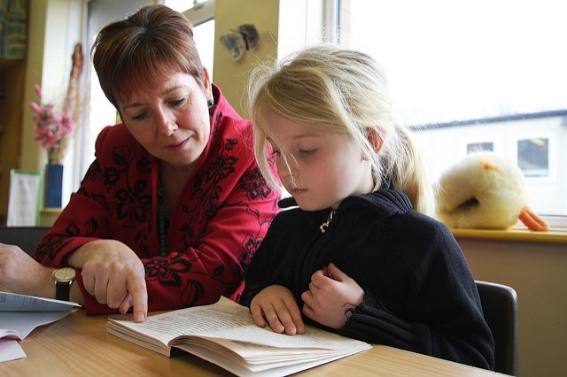 Photo of a girl reading with a teacher