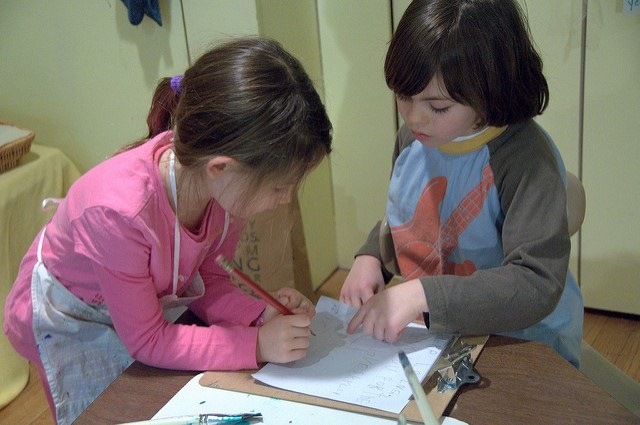 Photo of two girls writing on a piece of paper