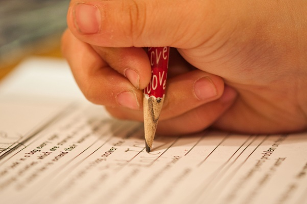 Photo of a child writing with a pencil