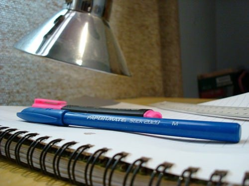Photo of a pen and notebook on a desk