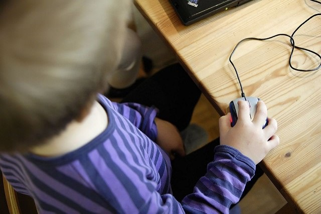 Photo of a boy using a computer mouse