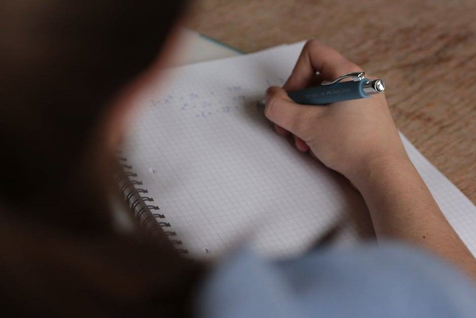 Photo of a girl writing on a notepad