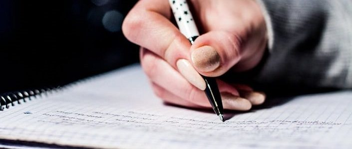 Photo of a woman writing on a notepad with a pen