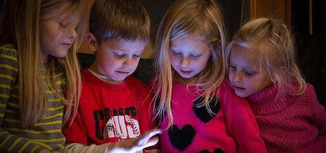 Photo of 4 children watching an ipad