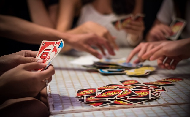 Screenshot of people playing cards around a table