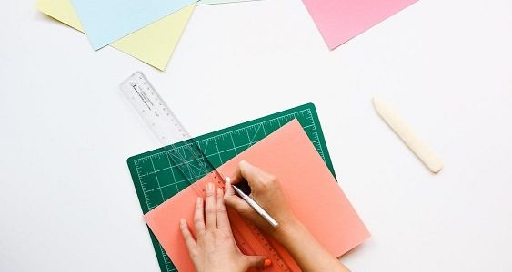 Photo of someone using a ruler on colourful paper