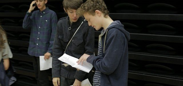 Photo of three boys receiving exam results at school