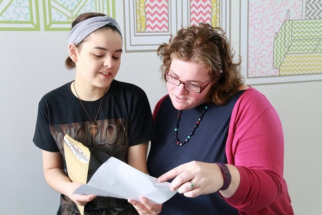 Photo of a student and teacher reading exam results together