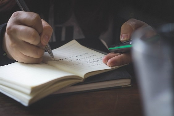 Photo of someone writing in a notepad