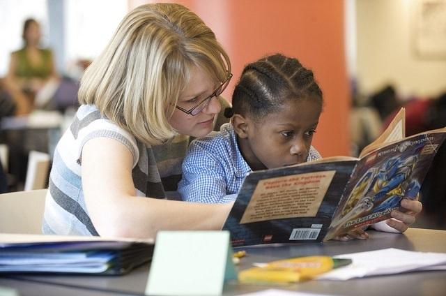 Photo of a boy reading with a teacher