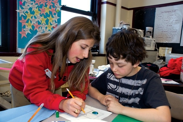 Photo of a tutor helping a child with school work