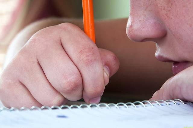 Photo of a boy writing on a notepad