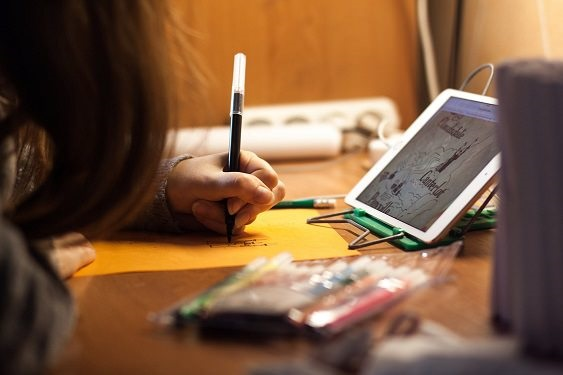 Photo of a girl writing on a desk