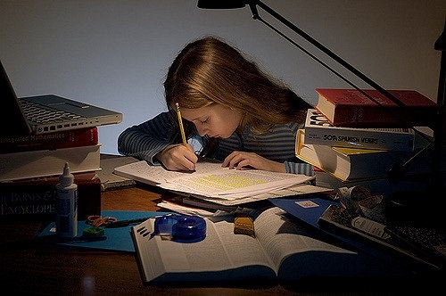Photo of a girl writing in a notebook on a desk