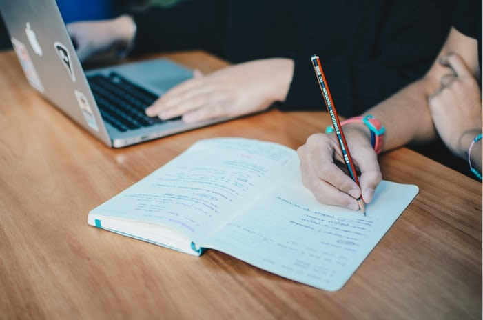 Photo of a student writing in a notepad